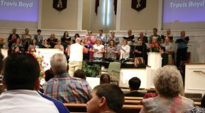 "Travis directs the reunion choir (at the Regency Park Baptist  Church 50th Anniversary service) in singing ""I Am Here"".  The service took place in the new Worship Center, which was built to replace the one destroyed by the tornado in 1999."